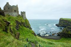 Dunluce Castle, Portrush, Northern Ireland. This is a picture of the now-ruined medieval Dunluce Castle, Portrush, Northern Ireland. With lush green grass and Royalty Free Stock Images