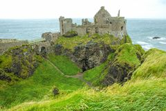 Dunluce Castle, Portrush, Northern Ireland. This is a picture of the now-ruined medieval Dunluce Castle, Portrush, Northern Ireland. With lush green grass and Stock Photo
