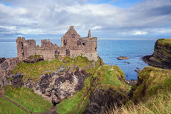 Dunluce castle ruins. Dunluce Castle is a now-ruined medieval castle in Northern Ireland. It is located on the edge of a basalt outcropping in County Antrim stock photos