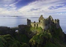 Dunluce slott och några öar av segla utmed kusten av nordligt - ireland. Royaltyfria Bilder