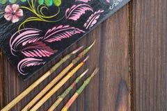 Dunne die verfborstels en schetsen op de donkere houten oppervlakte worden gelegd Stock Fotografie