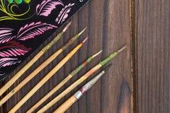 Dunne die verfborstels en schetsen op de donkere houten oppervlakte worden gelegd Royalty-vrije Stock Foto's
