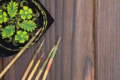 Dunne die verfborstels en schetsen op de donkere houten oppervlakte worden gelegd Stock Afbeeldingen