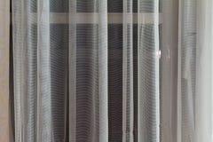 Dunne doorzichtige gordijnen die in een venster hangen stock foto's