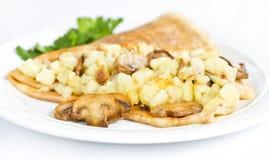 Dunne heerlijke pannekoek met aardappels en paddestoelen op wit stock foto's