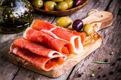 Dunne plakken van prosciutto met gemengde olijven op een scherpe raad Stock Fotografie