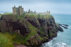 Dunnottar castle promontory and sea. Dunnottar castle, Stonehaven, near Aberdeen, Scotland. Side view of the evocative fortress ruins in a misty day, perched on Stock Images