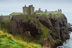 Dunnottar castle promontory side view. Dunnottar castle, Stonehaven, near Aberdeen, Scotland. Side view of the evocative fortress ruins in a misty day, perched Royalty Free Stock Photo