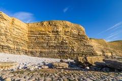 Dunraven fjärd- eller Southerndown strand, med kalkstenklippor Arkivfoton
