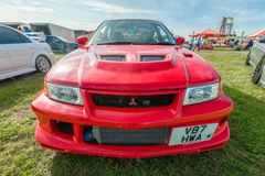 Mitsubishi Evo. Dunsfold, UK - August 26, 2017: Wide-angle closeup of a Mitsubishi Lancer Evolution sports-car at a gathering of classic and modern vehicles in Royalty Free Stock Photos
