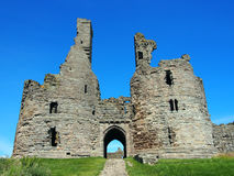 Dunstanborgh castle in northumbria main gateway. With blue sky Royalty Free Stock Photo