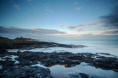 Dunstanburg Castle at sunset. Dunstanburgh Castle at sunset with gentle seas Royalty Free Stock Photography