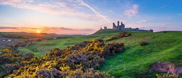 Dunstanburgh日落的城堡全景 免版税库存照片