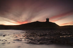 Dunstanburgh Castle. Sunrise from Saddle Rock stock photography