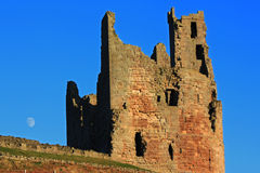 Dunstanburgh castle. Close up of the tower at Dunstanburgh Castle, Northumberland, England, with the moon rising in the sky in the background Stock Photography