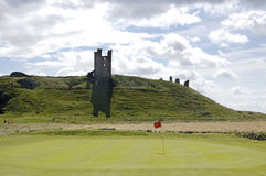 Dunstanburgh Castle and Golf green. One of the greens of Embleton Golf course and Dunstanburgh Castle Royalty Free Stock Photo