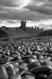 Dunstanburgh Castle Rocks. A view of Dunstanburgh Castle in Northumberland, from the dramatic stone beach Stock Photo