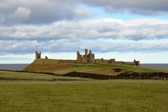 Dunstanburgh Castle ruins In Northumberland. Looking towards Bamburgh Castle in Northumberland, England Royalty Free Stock Photo