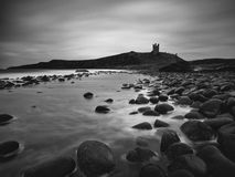 Dunstanburgh Castle. A view of Dunstanburgh Castle from Embleton Bay. A one minute exposure converted to monochrome Royalty Free Stock Photos