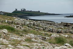 Dunstanburgh Castle View. Dunstanburgh Castle stands on a remote headland in Northumberland. The castle was built at a time when relations between King Edward II Stock Photos
