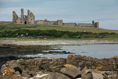Dunstanburgh Castle View. Dunstanburgh Castle stands on a remote headland in Northumberland. The castle was built at a time when relations between King Edward II Royalty Free Stock Images