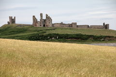 Dunstanburgh Castle View. Dunstanburgh Castle stands on a remote headland in Northumberland. The castle was built at a time when relations between King Edward II Royalty Free Stock Photo