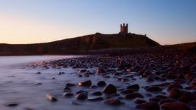 Dunstanburgh-Schloss an der Dämmerung Stockfotografie