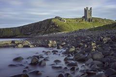 Dunstanburgh slott från strand Royaltyfri Bild