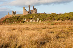 Dunstanburgh slott med tuvavåtmark i Northumberland Arkivbild