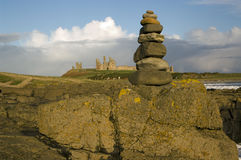 Dunstanburgh stone pile. A pile of stones with the ruined Dunstanburgh castle in the background royalty free stock photography