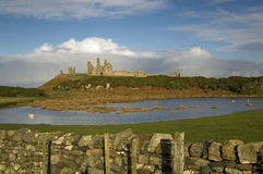 Dunstanburgh view. A view of this historic castle with a stone wall in the foreground royalty free stock images
