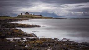 Dunstanburghkasteel naast het Overzees Stock Afbeeldingen