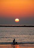 Dunstiger Sonnenuntergang mit Radfahrer Stockfotografie