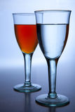 Duo. 2 glasses in a row with water and orange liquid inside stock photography
