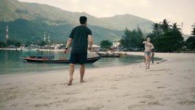 Duo, das auf dem Strand im Badminton spielt stock footage