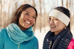 duo Ethnique-mélangé des amis féminins parlant en parc en hiver Photographie stock