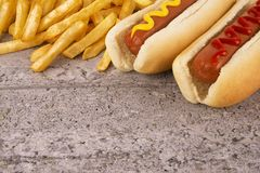 Duo of hot dogs and french fries on table. Fast food restaurant concept. stock image