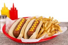 Duo of hot dogs and french fries on table. Fast food restaurant concept. stock photos