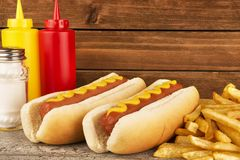 Duo of hot dogs and french fries on table. Fast food restaurant concept. royalty free stock images