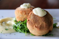 Duo of savory crab cakes served with lemon caper remoulade over a bed of arugula Stock Image