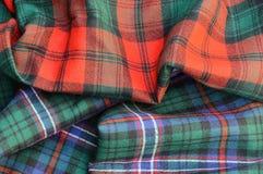 Duo of Tartan Plaid Fabrics. Multicolor duo of Scottish Tartan Plaid fabrics draped. Red, green, blue, black, white Royalty Free Stock Photos