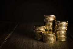 Gold coins in piles on a rustic background. Stock Photo
