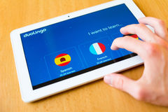 Duolingo. Man's hand use with his fingers tablet. Duolingo app on the screen. Duolingo is popular free language-learning platform royalty free stock photos
