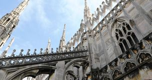 Gothic Milan Dome. Duomo di Milano cathedral church facede. Close up on its gothic spires on blue cloudy sky background, in Milan of Italy stock footage