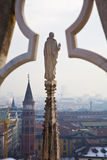 Duomo, Milan, Italy. A view over Milan from the roof of the Duomo with a gothic tower with statue in the foreground, Italy Stock Photography