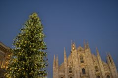 Duomofyrkanten av Milan dekorerade med julgranen och domkyrkan på solnedgången royaltyfri bild