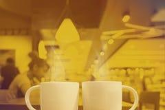 Duotone amarillo de dos tazas de café en el fondo del café, imita para arriba Imagenes de archivo