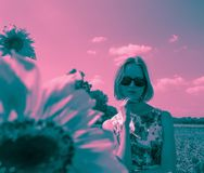 Duotone portrait of young woman in sunglasses. And floral dress staing in the field stock image