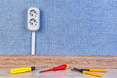 Duplex receptacle outlet with copy space. New euro wall outlet socket connected with frool with help of cable channel with copy space and hand tools on the floor royalty free stock photo