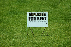 Duplexes fro rent yard sign on grass. Old yard sign in the middle of a field of grass that states Duplexes for rent Stock Image